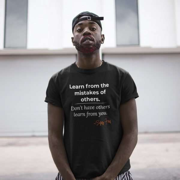 black man wearing a black tee that hase a safety management slogan on it.