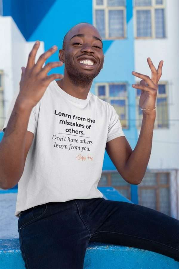 black man wearing a white tee that hase a safety management slogan on it.